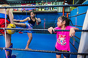 "18 DECEMBER 2104 - BANGKOK, THAILAND: A girl who wants to box works out after a sparring session at the Kanisorn gym. The Kanisorn boxing gym is a small gym along the Wong Wian Yai - Samut Sakhon train tracks. Young people from the nearby communities come to the gym to learn Thai boxing. Muay Thai (Muai Thai) is a Thai fighting sport that uses stand-up striking along with various clinching techniques. It is sometimes known as ""the art of eight limbs"" because it is characterized by the combined use of fists, elbows, knees, shins, being associated with a good physical preparation that makes a full-contact fighter very efficient. Muay Thai became widespread internationally in the twentieth century, when practitioners defeated notable practitioners of other martial arts. A professional league is governed by the World Muay Thai Council. Muay Thai is frequently seen as a way out of poverty for young Thais and Muay Thai camps and schools are frequently crowded. Muay Thai professionals and champions are often celebrities in Thailand.     PHOTO BY JACK KURTZ"