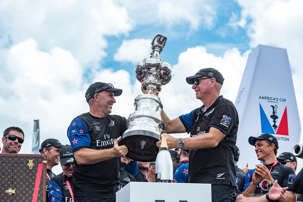 The Great Sound, Bermuda, 26th June 2017. Emirates Team New Zealand performance coach Ray Davies and Sir Stephen Tindall with the America's Cup.