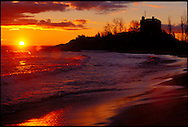 THE MARQUETTE LIGHTHOUSE IS SILHOUETTED AS THE SUN RISES ON LAKE SUPERIOR IN MARQUETTE MICHIGAN.