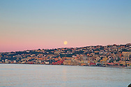 Full moon over Naples Italy at sunrise