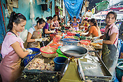 "26 SEPTEMBER 2012 - BANGKOK, THAILAND: Women package pieces of chicken at a stand in a Khlong Toey Market in Bangkok. Khlong Toey (also called Khlong Toei) Market is one of the largest ""wet markets"" in Thailand. The market is located in the midst of one of Bangkok's largest slum areas and close to the city's original deep water port. Thousands of people live in the neighboring slum area. Thousands more shop in the sprawling market for fresh fruits and vegetables as well meat, fish and poultry.     PHOTO BY JACK KURTZ"