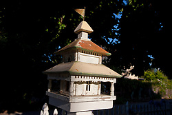 White bird house with metal roof and flag on top near sidewalk.