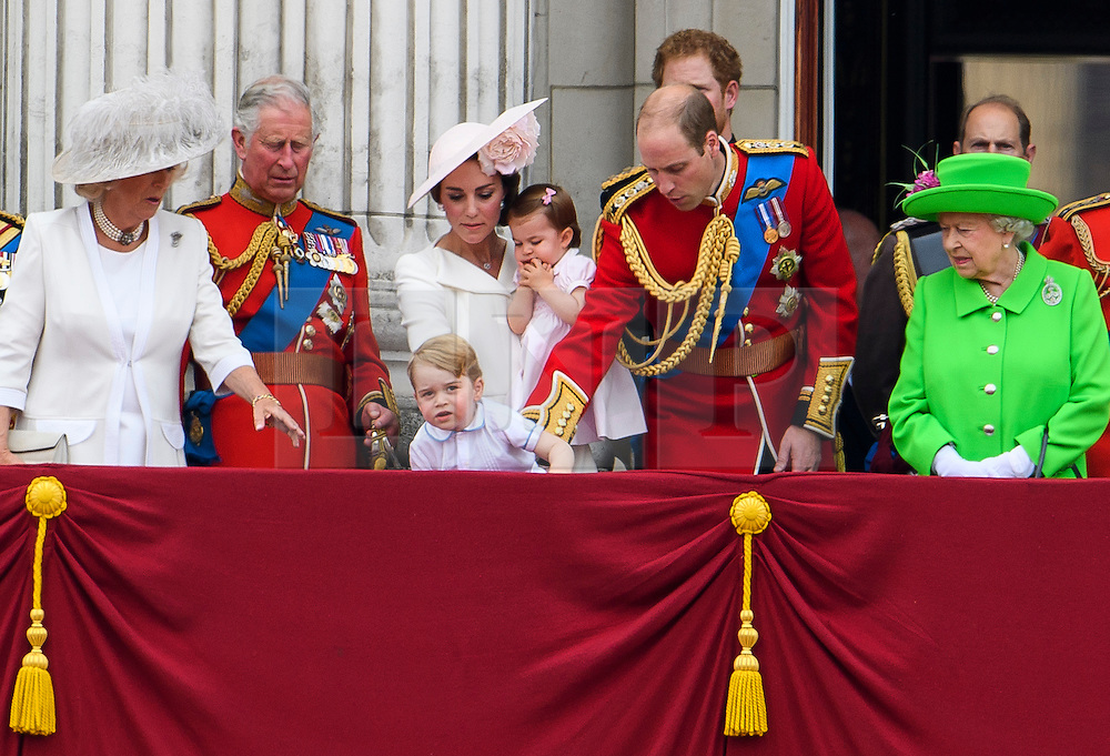 © Licensed to London News Pictures. 11/06/2016. London, UK. Members of the Royal Family attempt to stop PRINCE GEORGE from clambering to the edge of the balcony at Buckingham Palace,  during the Trooping The Colour ceremony in London. This years event is part of a weekend of celebration to mark the 90th birthday of Queen Elizabeth II, who is Britain's longest reigning monarch. Photo credit: Ben Cawthra/LNP