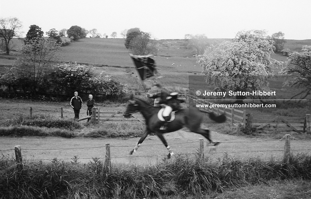 """Cornet Bruce Richardson gallops up Nipknowes hIll on his horse, carrying the Hawick town """"colours"""", during Hawick Common Riding week.. Scotland..PIC©JEREMY SUTTON-HIBBERT 2000.."""