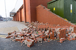 """© Licensed to London News Pictures. 12/02/2014. Aberystwyth, UK. Part of the Co-Op Supermarket  brick wall was blown down at the height of the winds. Winds gusting up to 107mph are battering the west wales coast at Aberystwyth.  Met Office """"red warnings"""",  the first of the winter , indicating risk to life and severe structural damage have been issued.. Photo credit : Keith Morris/LNP"""