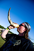 Metal fan  drinking from horn at festival with campsite behind, Bloodstock Outdoor festival, UK. 16/07/06