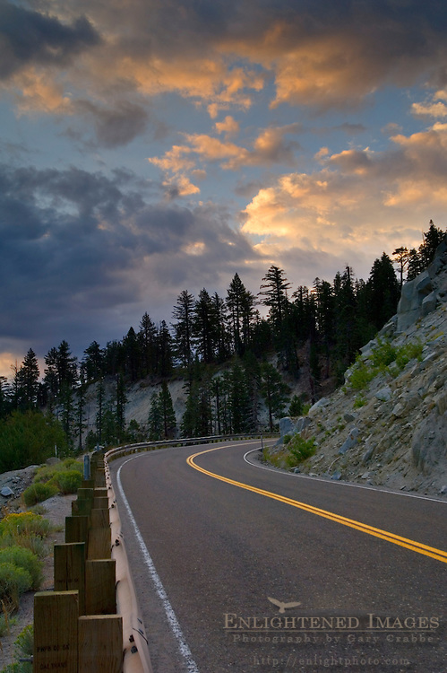 Sunrise light on storm clouds over curve mountain road, Emerald Bay State Park, South Lake Tahoe region, California