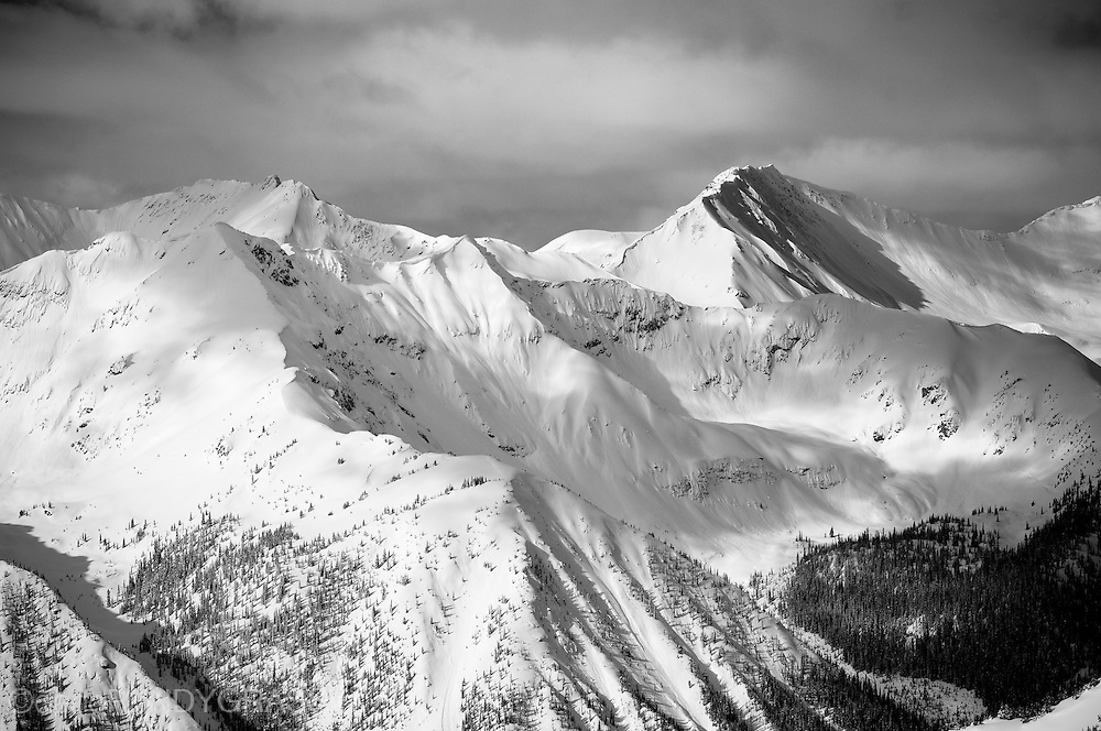 Windows of sun illuminate the mountains around Kicking Horse Resort in Golden, BC.
