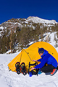 Backcountry skier and yellow dome tent in Little Lakes Valley, Inyo National Forest, Sierra Nevada Mountains, California