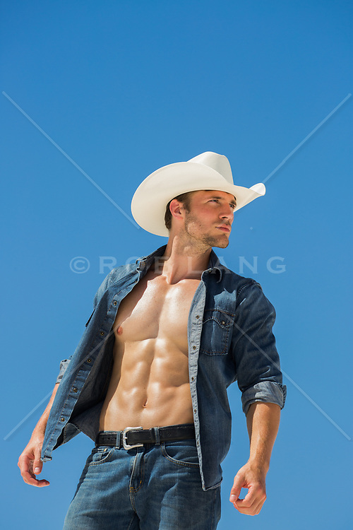 hot cowboy with an open shirt against blue sky