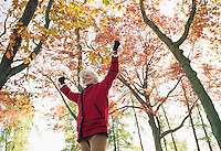 Mature Caucasian woman celebrating with arms held up above head while walking below Fall colored trees in a park setting.<br />