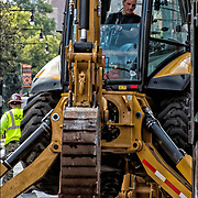 Backhoe operator excavating and lifting and moving material, soil to fill in underground street repairs replacing old water pipes.