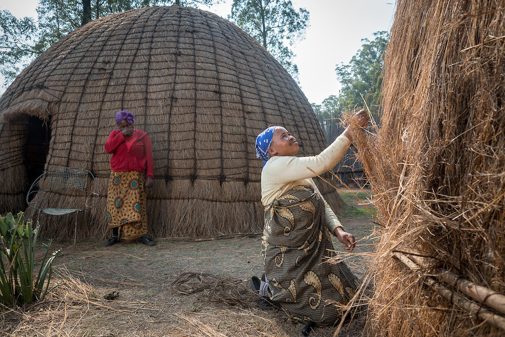 African women making beehive huts at the Mlilwane Wildlife Sanctuary in Swaziland Africa.