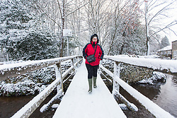 © Licensed to London News Pictures. 30/11/2017. Thornton Le-Dale UK. A lady walks across a snow covered bridge this morning after a night of heavy snow this in the village of Thornton Le-Dale in North Yorkshire.Photo credit: Andrew McCaren/LNP