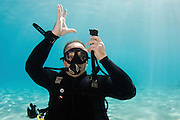 Deflate Buoyancy compensator Underwater Hand signs scuba diver demonstrates the sign language for divers.