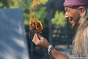 An Indian man demonstrating how to make a fire.