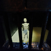 A sculptured figure is used to demonstrate the conditions in the solitary confinement cells in the dungeon of Hoa Lo Prison. The bars in the foreground are in the very small window in the door. Hoa Lo Prison, also known sarcastically as the Hanoi Hilton during the Vietnam War, was originally a French colonial prison for political prisoners and then a North Vietnamese prison for prisoners of war. It is especially famous for being the jail used for American pilots shot down during the Vietnam War.