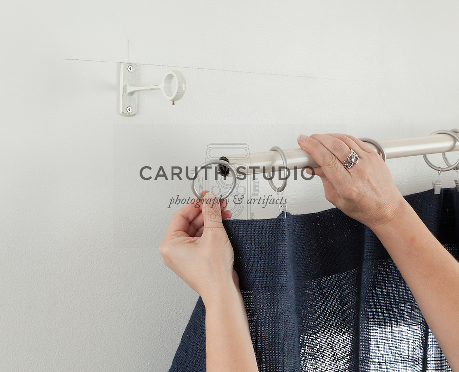 How to hang curtains: clipping curtain to rings and inserting onto curtain rod