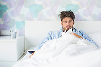 Portrait of sick man with thermometer in mouth reclining on bed at home