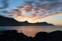 Sunset by Seyðisfjörður, a person looking out to sea. East fiords of Iceland.