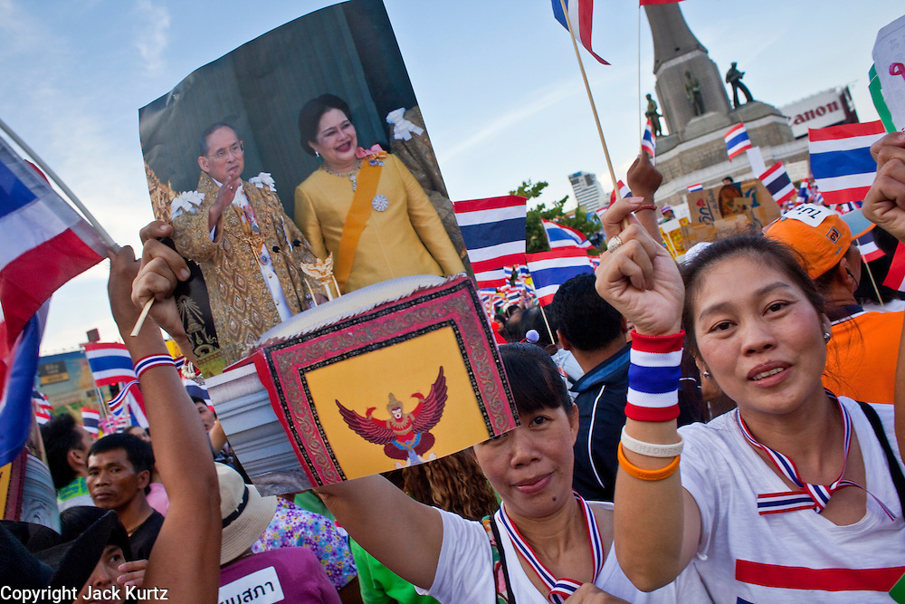"Apr. 18, 2010 - Bangkok, Thailand: Pink Shirts hold up a photo of Thai King Bhumibol Adulyadej and his wife, Queen Sirikit, during a peace rally in Bangkok Sunday. Thousands of so called ""Pink Shirts"" jammed the area around Victory Monument in Bangkok to show support the Thai Monarch, King Bhumibol Adulyadej, and against the Red Shirts, who are demonstrating just a few kilometres away in the Ratchaprasong area. The Pink Shirts claim to not support either of the other political factions who wear colors - the Red Shirts, who support deposed Prime Minister Thaksin Shinawatra and their opponents the Yellow Shirts, who are against Thaksin.   Photo By Jack Kurtz"