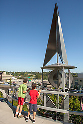 United States, Washington, Bellevue, boys at outdoor metal sculpture on terrace of Bellevue City Hall  MR