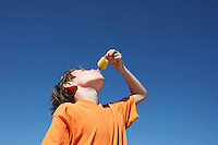 Boy (7-9) eating popsicle blue sky