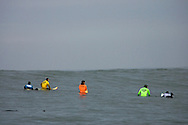 Jamie Sterling in blue, Brock Little in yellow, Shawn Rhodes in orange, Greg Long in green and Russel Smith in white wait for surf during heat 1 of the 2008 Mavericks Surf Contest on January 12 in Half Moon Bay