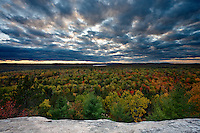 A sweeping view of intense and saturated autumn colors as seen fromLookout Point, Algonquin Provincial Park, Ontario, Canada. The scene is complimented by radiating and slightly colored clouds, shortly before sunset.