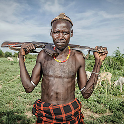 Dassanech man with kalashnikov looking after his cattle, Omo Valley, Ethiopia, Africa