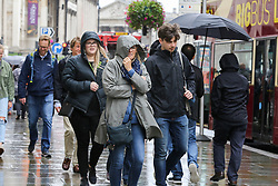 © Licensed to London News Pictures. 16/08/2019. London, UK. Tourists sheltering from the rain in Trafalgar Square. The Met Office has issued a severe weather alert for most of today, as almost a month's worth of rain is expected in many parts of the UK. Photo credit: Dinendra Haria/LNP
