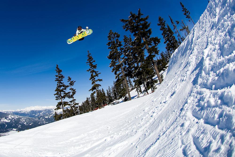 Professional snowboarder Meghann O'Brien catches air in the Terrain Park on Blackcomb Mountain, British Columbia, Canada