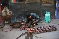 Iran, Isfahan, 29.08.2016: Ein Kupferschmied beim Säubern fertiger Gefäße, Basar in Isfahan. Provinz Isfahan, Esfahan, Zentral-Iran.