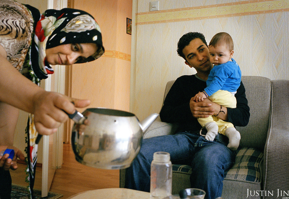 Dutch-Turkish teenager Hakan Dinc holds his brother while his mother pours water at home in Amsterdam. .Dinc, 16, was born in the Netherlands. His grandparents from his father?s side came from Turkey in 1971, and his mother came in 1987. Dinc feels more Turkish than Dutch, most of his friends are Turkish and he wants to marry a Turkish girl. During his time off he works in his uncle?s grocery store. Later, he wants to have his own shop. Dinc is following a Commerce course at a vocational school in Amsterdam. .Dinc likes music, pool and chilling out. He has a fourteen-year-old sister and a brother aged ten months. .Picture shot in Amsterdam in 2004 by Justin Jin. .
