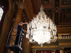 © Licensed to London News Pictures. 26/04/2012.  A worker at Goldsmiths Hall in London lights the candles in preparation for the The Duke and Duchess of Cambridge's arrival to take part in a Royal British Legion event. of the team from the Scott-Amundsen Centenary Expedition in the Guildhall today. Photo credit: Alison Baskerville/LNP