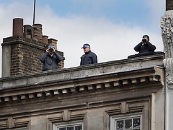© Licensed to London News Pictures. 10/04/2017. London, UK. Officers watch from a roof top as the funeral cortege carrying the coffin of policeman Keith Palmer leaves from Southwark after a service was held at the cathedral. PC Palmer was murdered just inside the main gates of Parliament by Westminster attacker Khalid Masood - an attack in which he also killed four people on Westminster Bridge. PC Palmer's funeral will take place at Southwark Cathedral today. Photo credit: Peter Macdiarmid/LNP