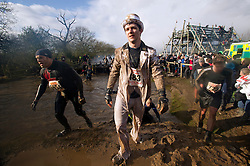 """©  London News Pictures. 27/01/2013.  A Competitor in costume wading through mud and freezing water as he is  pushed to the limits in the 2013 Tough Guy Challenge on January 27, 2013 in Wolverhampton, England. The event has been widely described as """"the toughest race in the world"""", with over one-third of the starters failing to finish in a typical year. Photo credit: Ben Cawthra"""