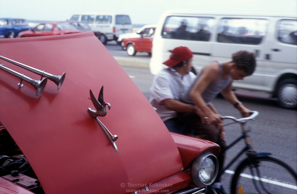 An old American car, bike riders and and traffic on Malecon, embankment in Habana, capital of Cuba.