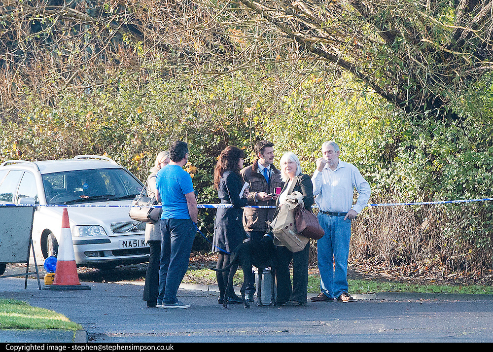 © Licensed to London News Pictures. 27/11/2014. Fetcham, UK. People gather at a police cordon.  A manhunt is under way across two counties after a man and woman were found stabbed to death in Surrey. The bodies were found at a house in Fetcham, near Leatherhead, after Surrey Police were alerted in the early hours.. Photo credit : Stephen Simpson/LNP