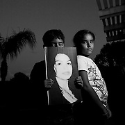 Portrait of 9-year-old twins, Isaac Alvarado and Rebecca Alvarado, hold a photo of their mother, Valeria Munique Tachiquin-Alvarado, who was shot and killed by a plain-clothed Border Patrol Agent in a residential suburb of San Diego. The agent alleged she had struck him and was carrying him on top of her car prompting him to fire in self defense.