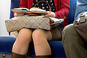 woman reading a book while traveling on a train