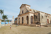 TRINIDAD, CUBA - OCTOBER 30, 2006: Unidentified people walk in front of the Church of the Holy Trinity in Trinidad, Cuba. Town of Trinidad in Cuba is declared a UNESCO World Heritage site.