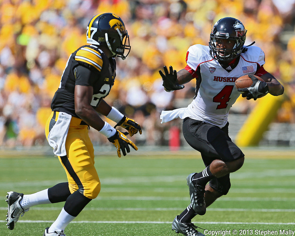 August 31 2013: Northern Illinois Huskies wide receiver Da'Ron Brown (4) tries to hold off Iowa Hawkeyes defensive back Jordan Lomax (27) after a catch during the first quarter of the NCAA football game between the Northern Illinois Huskies and the Iowa Hawkeyes at Kinnick Stadium in Iowa City, Iowa on August 31, 2013. Northern Illinois defeated Iowa 30-27.