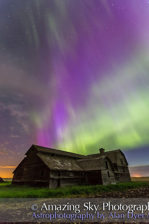An all-sky aurora with green and purple curtains, the night of June 7-8, 2014, starting up about 12:30 and going until dawn. This shot was near its peak, from the old barn site near home in southern Alberta. Foreground illumination is from the aurora and ambient sky -- the Moon had set. The Big Dipper is above the Barn. The purple colour is from blue scatttered sunlight hitting the red tops of the auroral curtains. This was with the 16-35mm lens at f/3.2 for 20 seconds at ISO 1600 with the Canon 6D.
