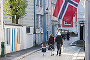 A family walks down a street in Bergen dressed in traditional festive garb in celebration of Syttende Mai, Norway's Constitution Day, celebrated on May 17th.