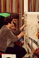 Amangul Ikhanova weaves an artistic pattern on a loom with her daughters Kuralai,  and Meruert, at her studio in the Artist's Union building in Almaty, Kazakhstan