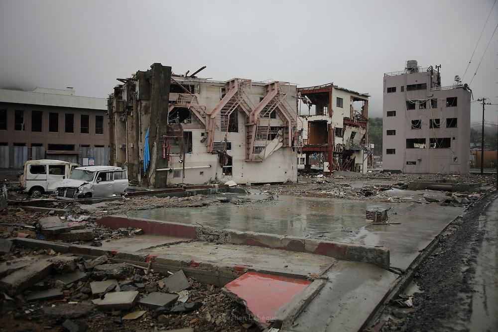 Onagawa n'existe plus - Juin 2011<br /> Le panorama se r&eacute;sume en une ville arrach&eacute;e, pli&eacute;e, broy&eacute;e, disparue ! Il ne reste du b&acirc;ti que des emplacements au sol &agrave; peine visibles. Quelques ossatures &eacute;vid&eacute;es, des b&acirc;timents fr&ecirc;les ou des blocs de plusieurs &eacute;tages en b&eacute;ton simplement couch&eacute;s  s&eacute;parpillent sur ce qu&eacute;tait Onagawa. .Lun deux encore debout comporte les marques visibles de la charge de leau jusquau quatri&egrave;me &eacute;tage.