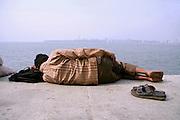 man catching a nap on sidewalk, mumbai, india