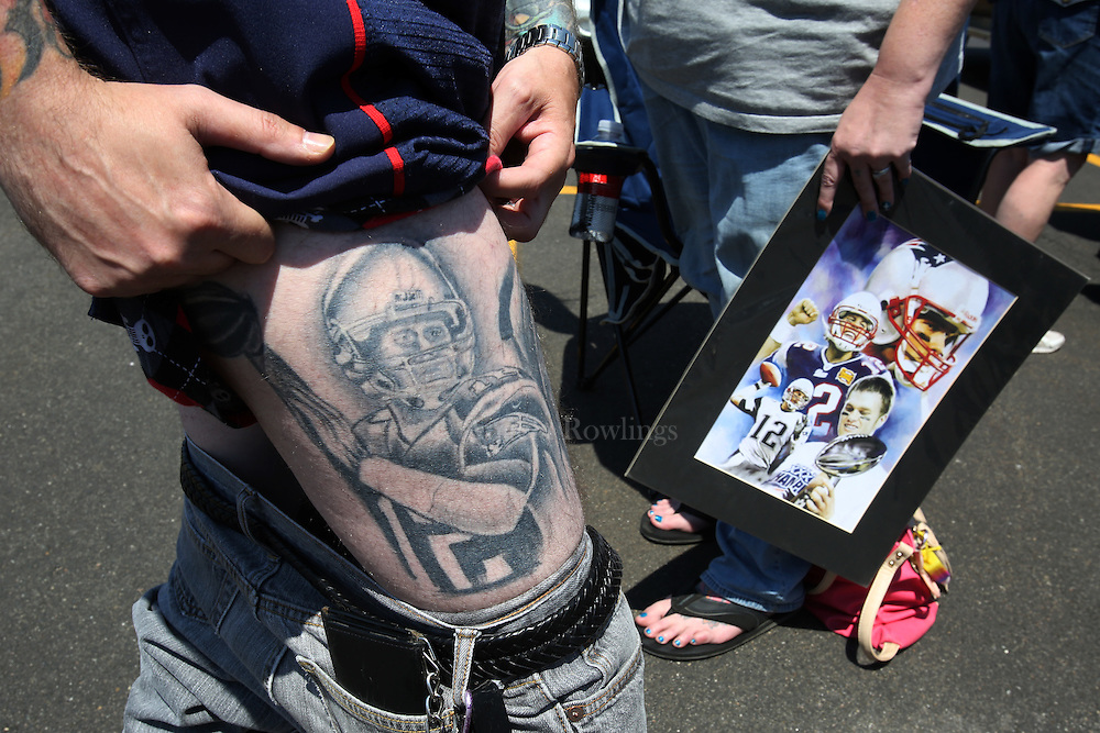 """(Foxboro, MA - 5/24/15) Paul Goodrow of Watertown shows off his Tom Brady tattoo as his wife, Kellie Goodrow holds a poster of the quarterback during a """"Free Tom Brady"""" rally at Gillette Stadium, Sunday, May 24, 2015. The couple married on May 9, but said they are postponing their honeymood to Bermuda due to Brady's controversial penalty. Staff photo by Angela Rowlings."""