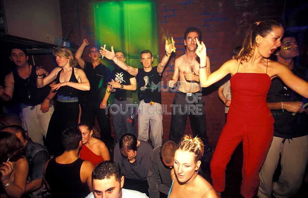 A crowd of people dance in a night club, U.K, 1990s.